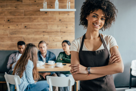 Photo for Smiling african american waitress standing with customers sitting behind in cafe - Royalty Free Image