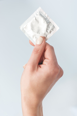 Foto de cropped view of woman holding condom in hand isolated on white - Imagen libre de derechos