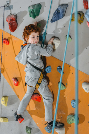 Foto de Full-length shot of little boy in a harness climbing a wall with grips at gym and looking at camera - Imagen libre de derechos