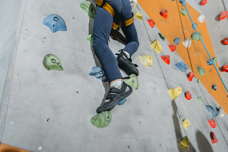 Photo pour Cropped shot of a little boy in harness climbing a wall with grips at gym - image libre de droit