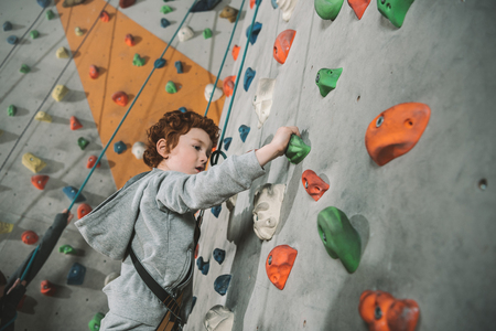Photo pour Half-length shot of little boy in a harness climbing a wall with grips at gym - image libre de droit