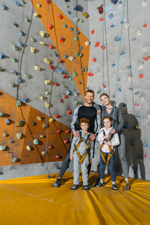 Photo pour Family with children standing together near climbing walls at gym and looking at camera - image libre de droit