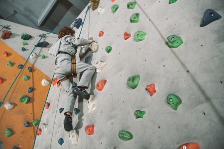 Photo pour Low-angle shot of little red-headed boy climbing a wall - image libre de droit