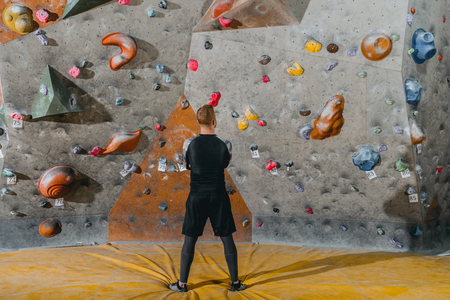Photo pour Full-length shot of a young man in sportive attire posing in front of climbing wall - image libre de droit