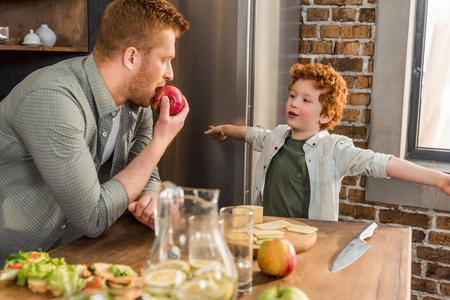 Foto de little boy looking at father eating fresh apple at home - Imagen libre de derechos