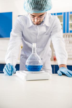 Foto de Young pharmacy worker weighing a flask with reagent in laboratory - Imagen libre de derechos