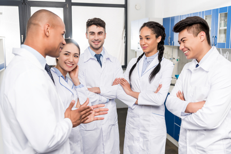 Foto de Team of young doctors in lab coats discussing work in laboratory - Imagen libre de derechos