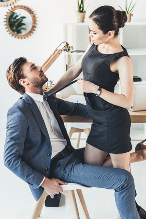 Photo pour Woman in black dress and high heels standing over a man in suit sitting in a chair and pulling him by the necktie - image libre de droit