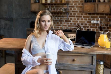 Photo pour Young sensual woman in lingerie having her morning coffee in kitchen  - image libre de droit