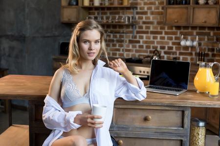 Foto de Young sensual woman in lingerie having her morning coffee in kitchen  - Imagen libre de derechos