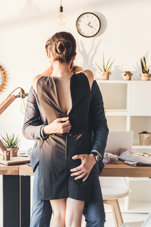 Photo pour Man in a suit making out with woman and unzipping her dress - image libre de droit