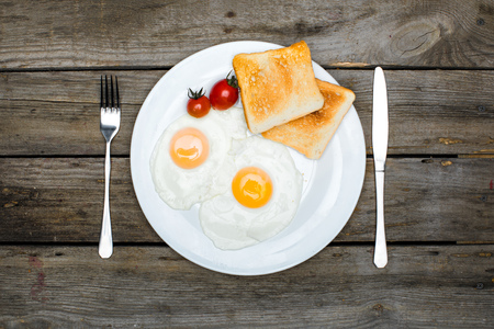 Photo pour top view of fresh tasty breakfast with fried eggs and toasts on plate - image libre de droit