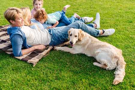 Photo pour happy young family with golden retriever dog resting on grass at picnic - image libre de droit