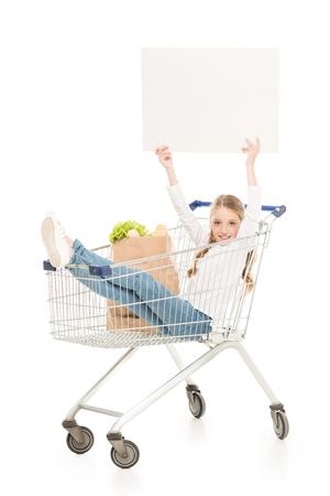 Foto de happy little girl sitting in shopping cart isolated on white - Imagen libre de derechos