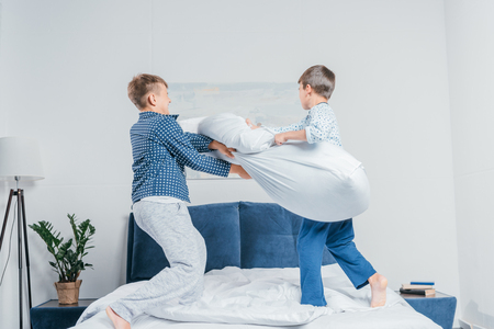 Photo pour little boys in pajamas jumping on bed and having pillow fight at home - image libre de droit