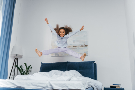 Foto de happy little african american girl in pajamas jumping on bed - Imagen libre de derechos