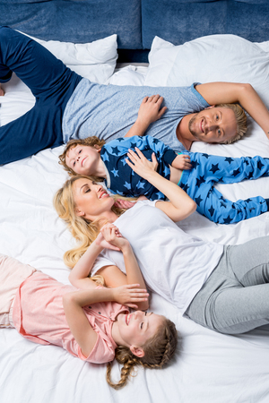 Foto de top view of happy young family lying together in bed - Imagen libre de derechos