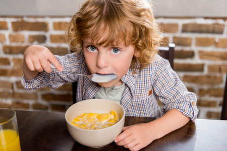Photo for adorable little boy eating corn flakes and looking at camera - Royalty Free Image