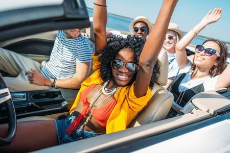 Foto de multiethnic smiling friends riding car while traveling together - Imagen libre de derechos