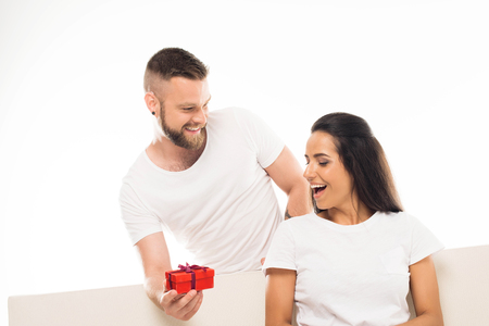 Photo for 'portrait of young attractive man surprising his girlfriend by gift, isolated on white - Royalty Free Image