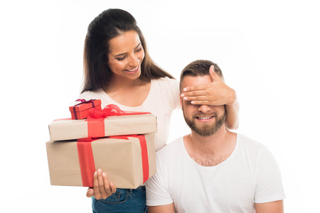 Photo for 'portrait of young attractive woman surprising her boyfriend by gifts, isolated on white - Royalty Free Image