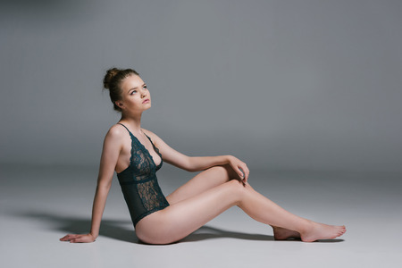 Photo pour attractive sensual woman with slim body wearing lace bodysuit and sitting on grey - image libre de droit