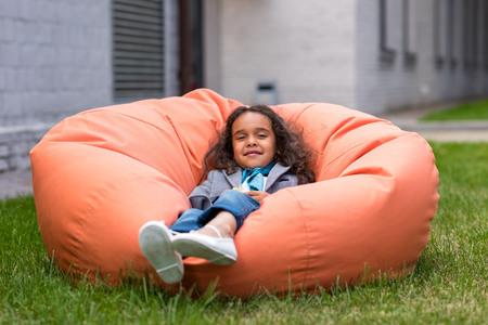 Foto de cute little african american girl lying on bean bag chair and looking at camera - Imagen libre de derechos