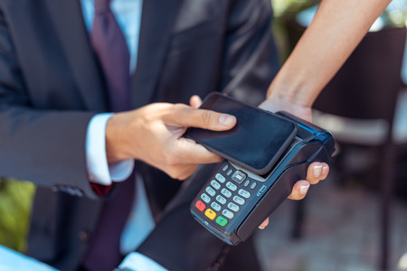 Photo pour Close-up view man paying with NFC technology on smartphone  - image libre de droit