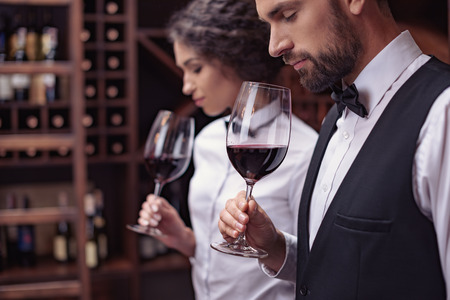 Photo pour Two sommeliers, male and female tasting red wine in cellar - image libre de droit
