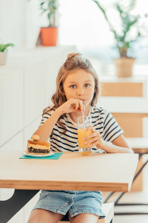 Photo pour cute little girl with cake and orange juice sitting in cafe - image libre de droit