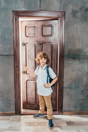 Foto de cute little boy going to school, standing next to door - Imagen libre de derechos