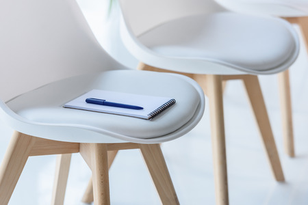 Foto per Notepad and pen on chair in modern office - Immagine Royalty Free