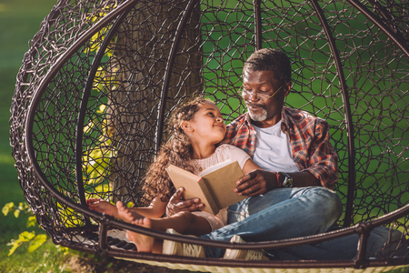 Foto de happy african american grandchild reading book while sitting in swinging hanging chair with grandfather - Imagen libre de derechos