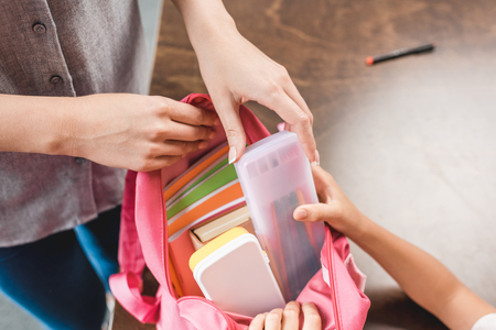 Photo pour cropped shot of mother and daughter preparing backpack with school supplies - image libre de droit