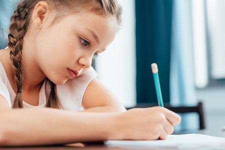 Foto de focused serious little girl writing homework - Imagen libre de derechos