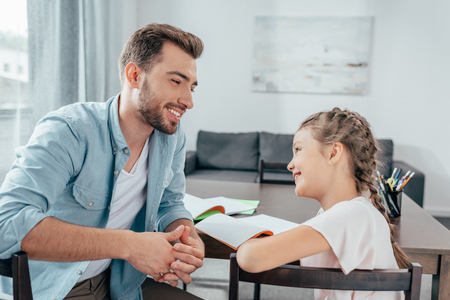 Photo pour young father doing homework with little daughter - image libre de droit