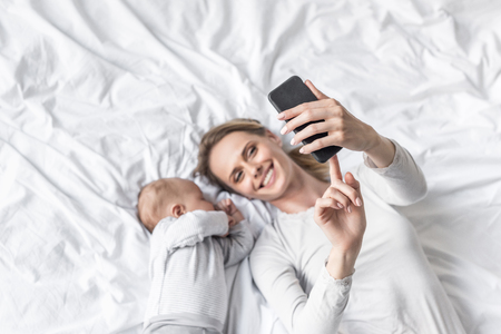 Foto de happy mother taking selfie with little sleeping baby   - Imagen libre de derechos