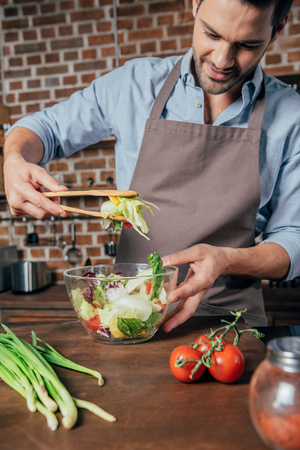 Photo pour handsome young man mixing salad - image libre de droit