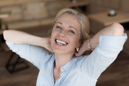 Photo for portrait of cheerful mature woman with hands behind head smiling at camera - Royalty Free Image