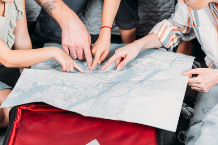 Photo pour cropped shot of family pointing at map while planning trip - image libre de droit
