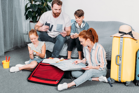 Photo pour family planning trip with luggage and map in bedroom - image libre de droit