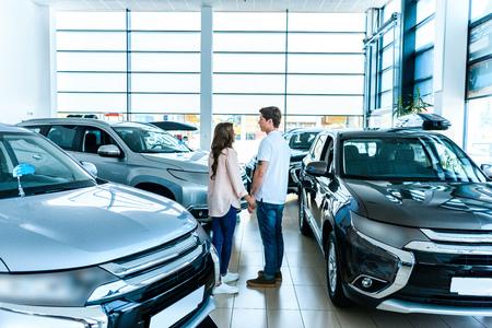 Photo pour Boyfriend and girlfriend standing face to face in a car showroom - image libre de droit