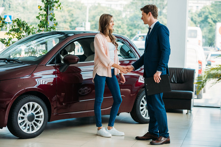 Photo pour Manager shaking hands to customer after selling a car in showroom - image libre de droit
