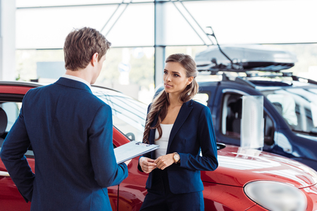 Photo for Female and male managers of car showroom standing and talking about work - Royalty Free Image