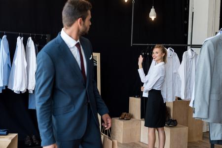 Foto de young businessman looking at young woman waving hand in boutique - Imagen libre de derechos