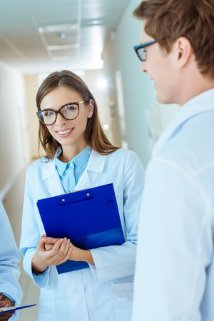 Photo for Young medical intern in lab coat and glasses, holding clipboard and smiling - Royalty Free Image