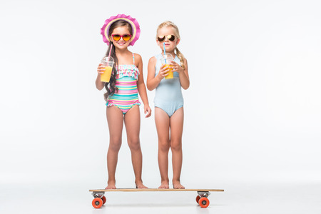 Photo pour adorable little girls in sunglasses and swimsuits drinking orange juice while standing on skateboard - image libre de droit