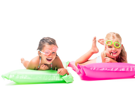 Photo for happy little girls lying on swimming mattresses and smiling at camera isolated on white  - Royalty Free Image