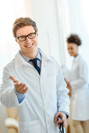 Photo for Young doctor in lab coat and glasses smiling cheerfully and holding out his hand - Royalty Free Image