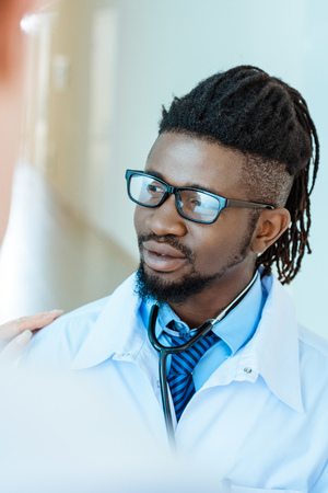 Photo for An african-american medical intern in lab coat and glasses - Royalty Free Image